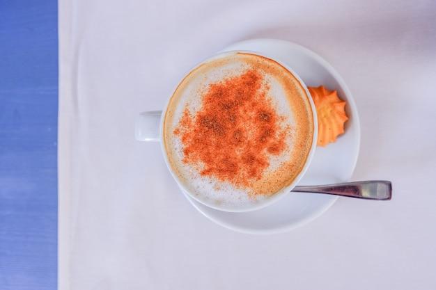 Weiße tasse cappuccino mit zimt auf dem hellblauen tisch mit weißer serviette, draufsicht. guten morgen kaffee. heißgetränkekonzept. speicherplatz kopieren