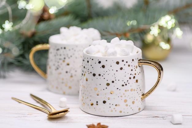 Weiße tasse cappuccino oder kakao mit weihnachtsbaum auf dem buckground des goldbokeh, heißes neujahrsgetränk.