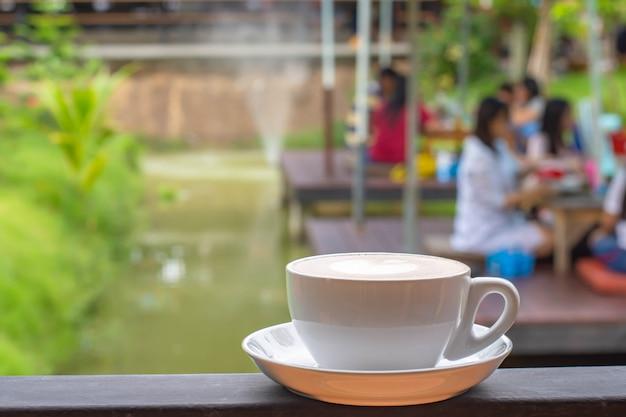 Weiße tasse der kaffeetassen mit dem herzförmigen make-up auf eisenbalkonen