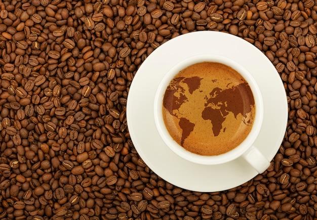 Weiße tasse espresso mit weltkarte auf schaum über hintergrund geröstete kaffeebohnen