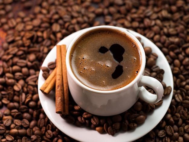 Weiße tasse espressokaffee auf gerösteten arabica-kaffeebohnen