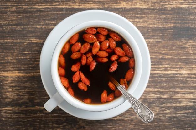 Weiße tasse frischen morgen-goji-kaffees auf holztisch, draufsicht, nahaufnahme. schwarzer heißer kaffee mit ganzen roten goji-beeren