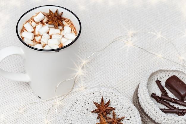 Weiße tasse heiße schokolade mit marshmallows und süßigkeiten und dekoriert leuchtende girlande