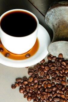 Weiße tasse heißen kaffees in kaffeebohnenstreuung,