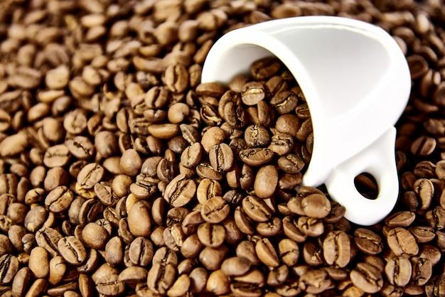 Weiße tasse in kaffeebohnen.