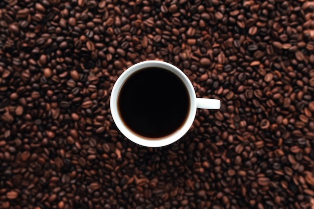 Weiße tasse kaffee auf einem bündel gerösteten kaffeebohnenhintergrund. hochwertiges foto