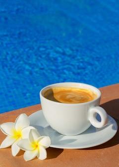 Weiße tasse kaffee in der nähe von blauem wasser des pools mit kopierraum