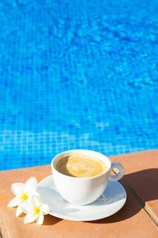Weiße tasse kaffee in der nähe von blauem wasser des pools