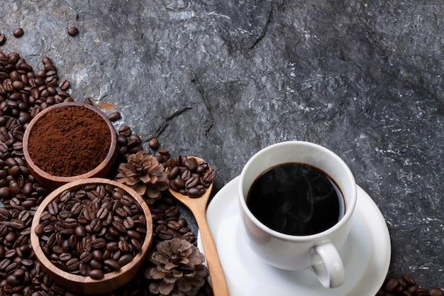Weiße tasse kaffee, kaffeebohnen in der hölzernen tasse, holzlöffel auf schwarzem stein