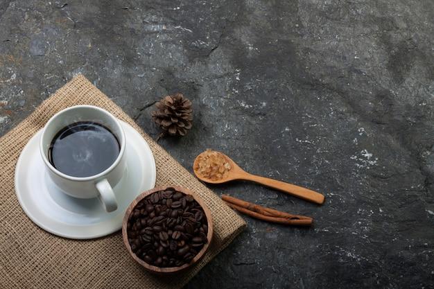 Weiße tasse kaffee, kaffeebohnen in holztasse, trockene kiefer auf sackleinen auf schwarzem stein