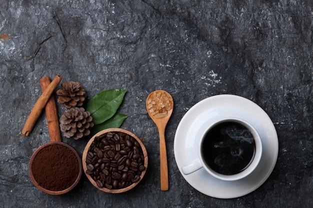 Weiße tasse kaffee, kaffeebohnen in holztasse, zucker in holzlöffel kiefer und blatt auf schwarzem stein