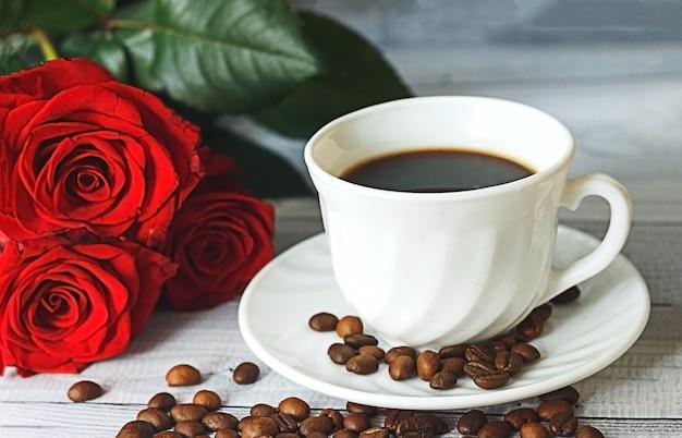 Weiße tasse kaffee kaffeebohnen und rote rosen auf hellgrauem hintergrund romantisches frühstückskonzept