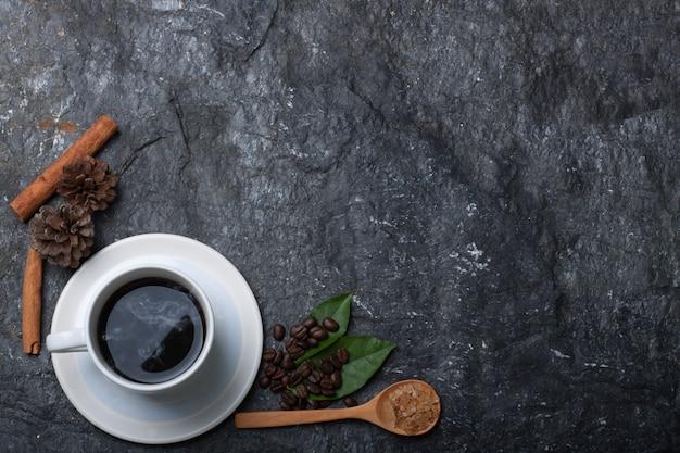 Weiße tasse kaffee, kaffeebohnen, zucker in holzlöffel kiefer und blatt auf schwarzem stein