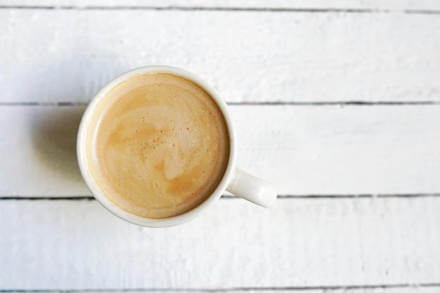 Weiße tasse kaffee, kopien-raum auf weißem hölzernem