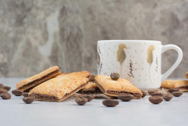 Weiße tasse kaffee mit crackern und kaffeebohnen auf weißem hintergrund. hochwertiges foto