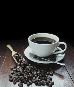 Weiße tasse kaffee mit holzlöffel voller kaffeebohnen auf dem tisch