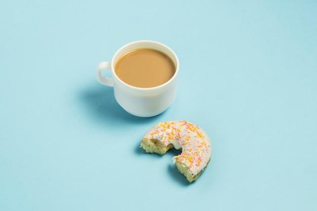 Weiße tasse, kaffee oder tee mit milch und bitten off frischer leckerer süßer donut auf blauem grund. fast-food-konzept, bäckerei, frühstück. minimalismus.