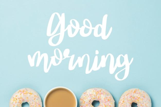 Weiße tasse, kaffee oder tee mit milch und frischen leckeren donuts auf blau. bäckereikonzept, frisches gebäck, leckeres frühstück, fast food.