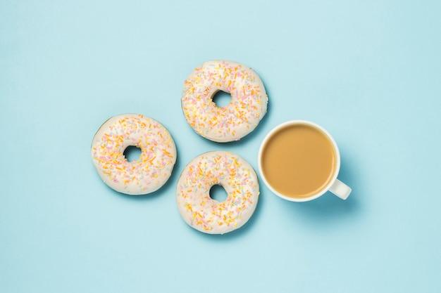 Weiße tasse, kaffee oder tee mit milch und frischen leckeren donuts auf einem blauen hintergrund. bäckereikonzept, frisches gebäck, leckeres frühstück, fast food.
