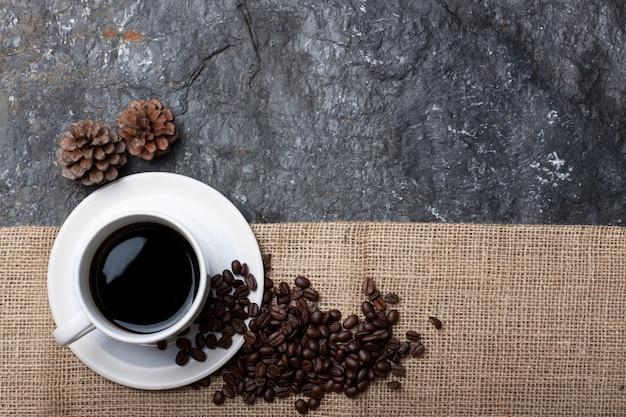 Weiße tasse kaffee, trockene kiefer auf sackleinen auf schwarzem stein