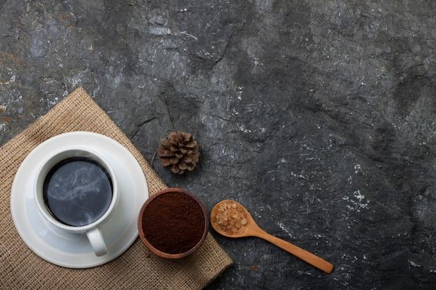 Weiße tasse kaffee, trockene kiefer, zucker im holzlöffel auf sackleinen auf schwarzem stein