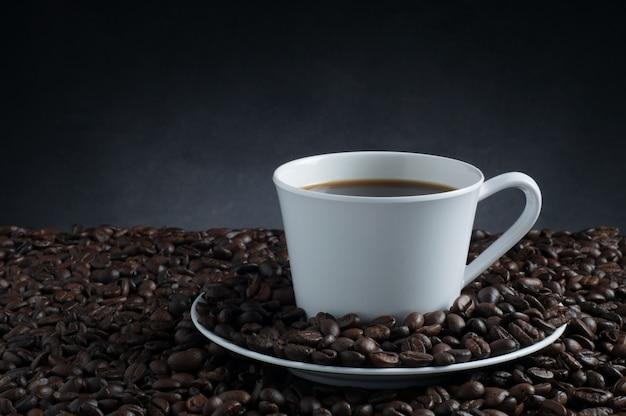 Weiße tasse kaffee und kaffeebohnen mit schwarzer farbe