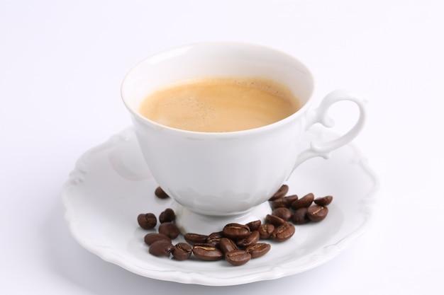 Weiße tasse kaffeebohnen lokalisiert auf keramischer porzellanzichorie des weißen hintergrundes