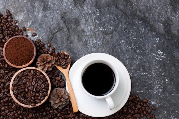 Weiße tasse kaffeeset, kaffeebohnen in der hölzernen tasse, holzlöffel auf schwarzem stein