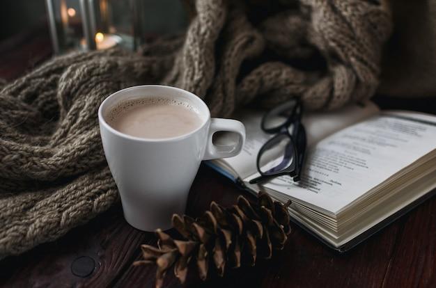 Weiße tasse kakao auf einem alten holztisch mit einem unterhaltsamen buch und einer lesebrille.