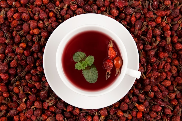 Weiße tasse kräuter-hibiskus-tee und getrocknete hagebutten.
