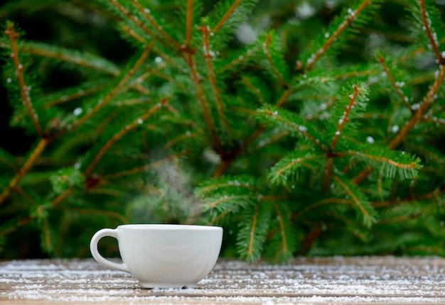 Weiße tasse mit einem getränk im schnee neben baum