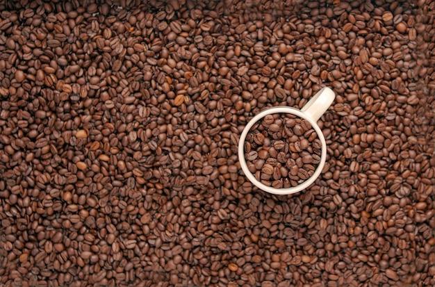 Weiße tasse mit gerösteten bohnen auf dem braunen texturhintergrund des kaffeehintergrundes draufsicht