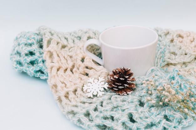 Weiße tasse mit gestricktem schal