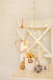 Weiße tasse mit goldenen kugeln und wunderkerzen zwerg mit langem bart weiße weihnachtsherzen tannenzapfen