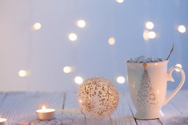 Weiße tasse mit goldenen weihnachtsdekorationen auf weißem holztisch