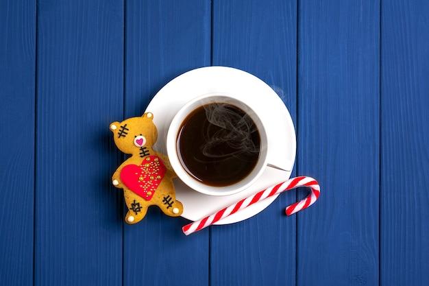 Weiße tasse mit heißem kaffee mit dampf, lebkuchen, zuckerstangen auf blauem holz