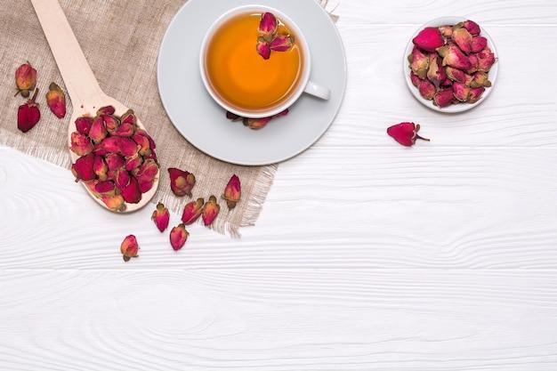 Weiße tasse mit heißem tee. ein holzlöffel mit getrockneten blütenknospen auf einer leinenserviette