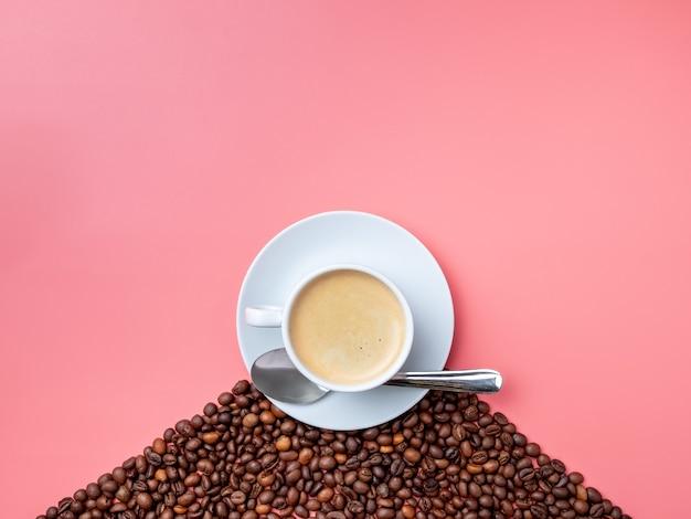 Weiße tasse mit heißen kaffee-kaffeebohnen und einem metalllöffel auf einem rosa hintergrund