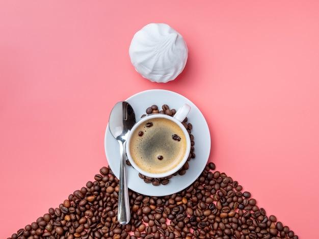 Weiße tasse mit heißen kaffee-kaffeebohnen und marshmallows auf einem rosa hintergrund