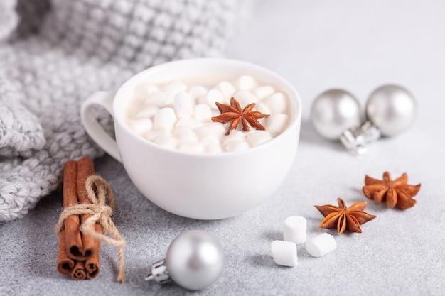 Weiße tasse mit heißer schokolade und marshmallow, pullover, zimt
