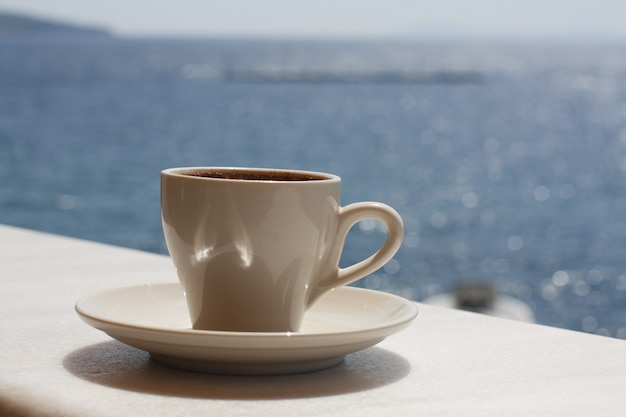 Weiße tasse mit kaffee auf dem hintergrund des meeres. sonniger tag, urlaub am meer. genussmoment. eine tasse kaffee am meer genießen.
