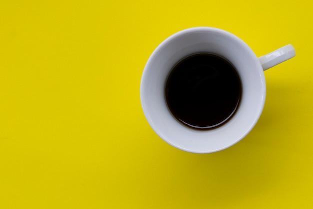 Weiße tasse mit kaffee auf der gelben tafel. draufsicht