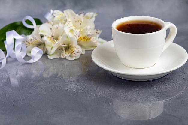 Weiße tasse mit kaffee auf grauem hintergrund. ein strauß orchideen mit einem band im hintergrund verschlungen. banner, glückwunsch zum urlaub. speicherplatz kopieren.