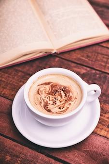 Weiße tasse mit kaffee, hinter einem offenen buch