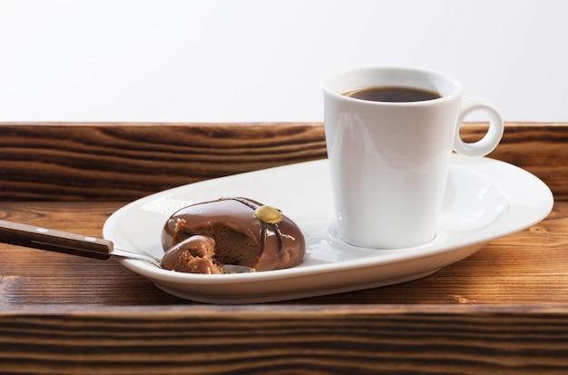 Weiße tasse mit kaffee mit schokoladencupcake