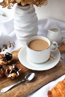 Weiße tasse mit kaffee steht auf einem leichten tuch. kunstlärm