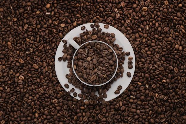 Weiße tasse mit kaffeebohnen.