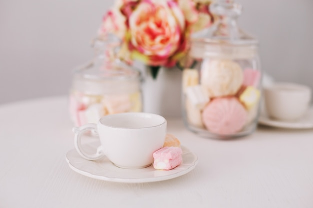 Weiße tasse mit marshmallows auf weißem hintergrund. romantisches frühstück. konzept von feiertag, geburtstag, ostern, 14. februar, 8. märz. flach liegen