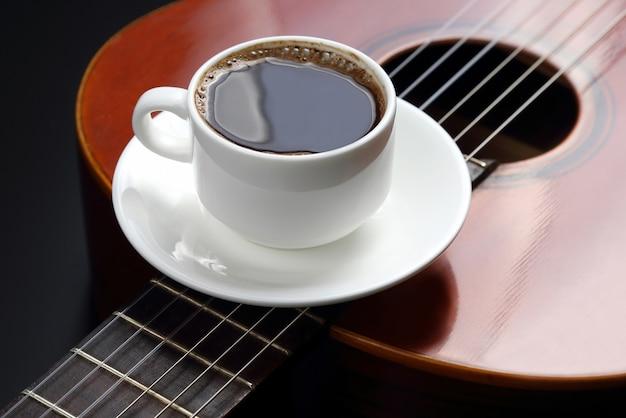Weiße tasse mit schwarzem kaffee, der auf der akustikgitarre liegt