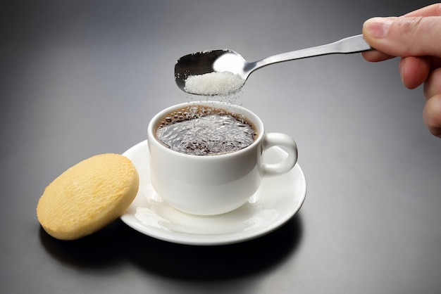 Weiße tasse mit schwarzem kaffee und löffel mit zucker